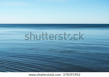 Still Baltic sea and clear blue sky. - stock photo