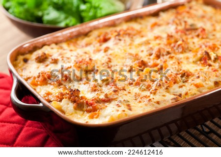Still bubbling hot from the oven. This lasagna was made with layers of slow simmered ragu, bechamel sauce, parmesan cheese and lasagna noodles. Fresh salad in the background.  - stock photo