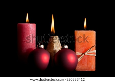 Still burning candles and Christmas balls on a black background