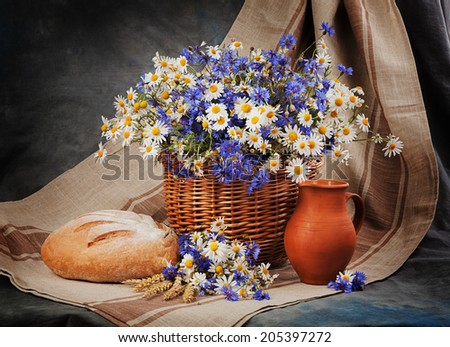 Still Daisies and cornflowers in the basket. Bread and milk on the table - stock photo