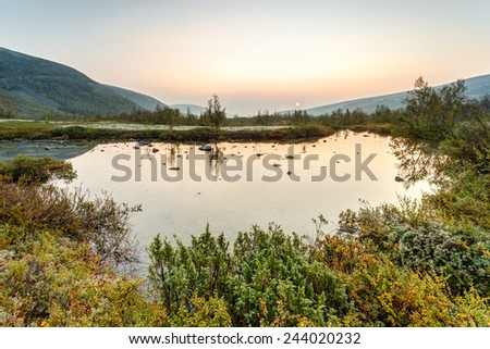 Still freshwater polygonal lake with willows and juniper on its edge in cold morning valley of Tuljok in Hibiny mountains above the Arctic Circle, Russia - stock photo