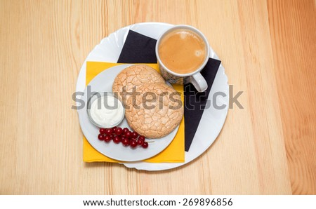 still life: a Cup of coffee and biscuits on plate on wooden table - stock photo