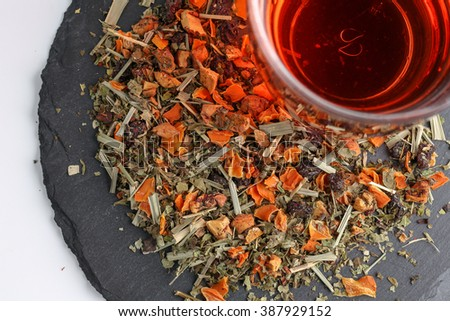 Still life, aromatic dry tea with fruits and petals, close up with a glass of tea on white background, selective focus  - stock photo