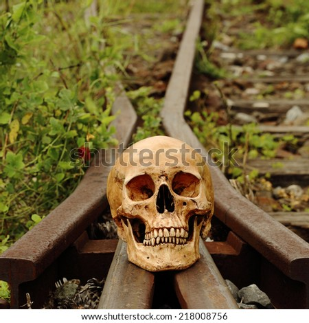 Still life art photography on death concept skull at old railroad - stock photo
