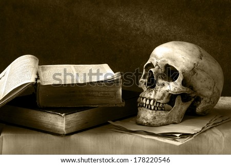 still life art photography on human skull  with open book on desk