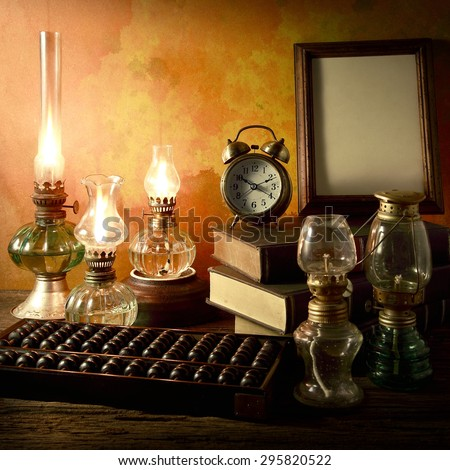 Still life art photography wisdom concept with alarm clock books oil lantern lamps wood abacus on vintage background environment - stock photo