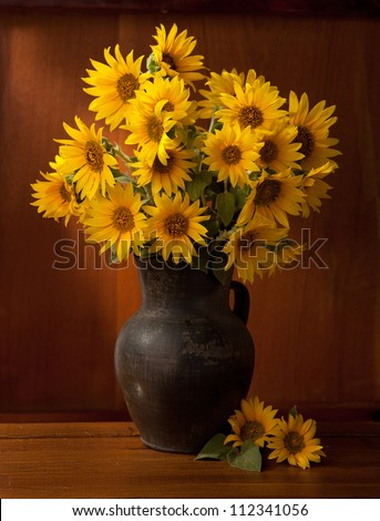 Still life. Beautiful Sunflowers in  old clay pot against a wooden wall - stock photo