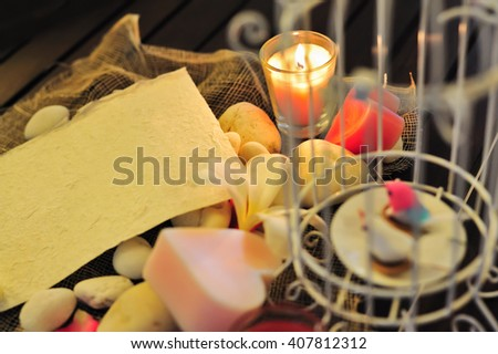 still life blank paper note to fill text under candle light with flower over decorated background for love theme and valentine concept. - stock photo