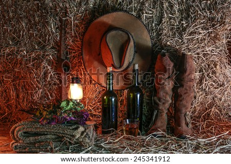 Still life, boots and hat on pile straw - stock photo