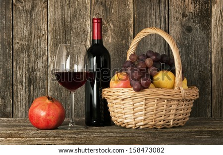 Still-life. Bottle of red wine, glass and basket with fruits - stock photo