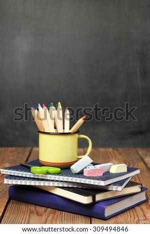 Still life, business, education concept. Chalk pieces, notebooks and pencils in a mug on a wooden table with chalkboard. Selective focus, copy space, school background - stock photo