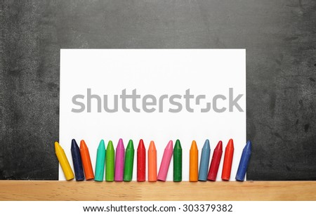 Still life, business, education concept. Empty sheet of paper with crayons on a dusty chalkboard. Selective focus, copy space background, top view - stock photo