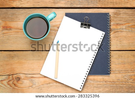 Still life, business, education concept. Office supplies, mug with coffee, notepad, staple and pencil on a wooden table. Selective focus, copy space background, top view - stock photo
