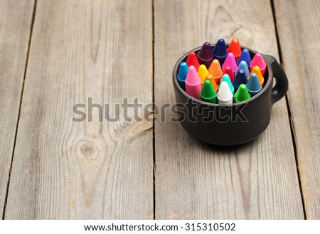Still life, business, education concept. School, office supplies, crayons (pencils) in a mug on a wooden table. Selective focus, copy space background - stock photo