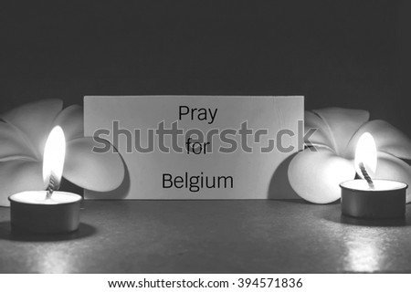 still life candle with flower and note pray for Belgium background,candle flame at night. - stock photo