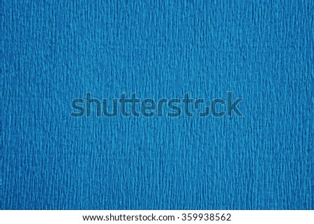 Still life close up detail of a wrinkly bright blue rough grungy piece of paper with vertical lines and thick texture. Full frame background with texture detail. Monotone cyan backdrop blank page. - stock photo