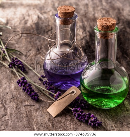 Still Life Close Up of Colorful Purple and Green Essential Aromatherapy Oils in Corked Vials on Textured Stone Surface with Sprigs of Fresh Lavender and Blank Paper Tag - stock photo