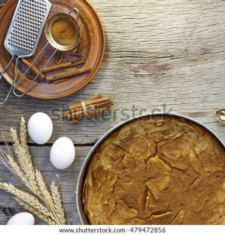 Still life. Closeup of apple pie with cinnamon, bunch of ears of corn and eggs on a wooden table. rustic style, top view