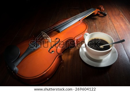 Still life coffee cup with violin on wood surface. - stock photo