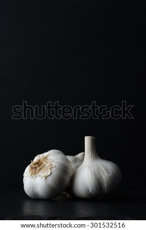 Still life composition of three whole garlic bulbs on black slate against black background. - stock photo
