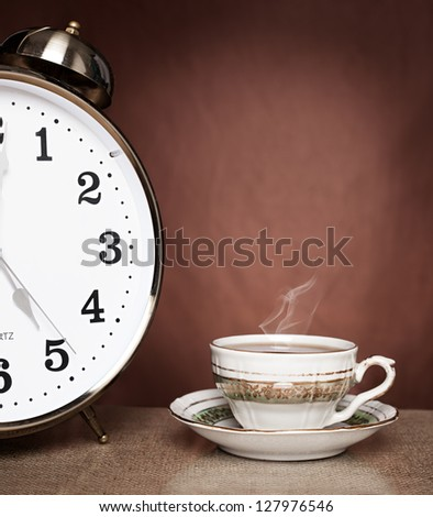 still life concept picture of teacup and a alarm clock on brown background - stock photo