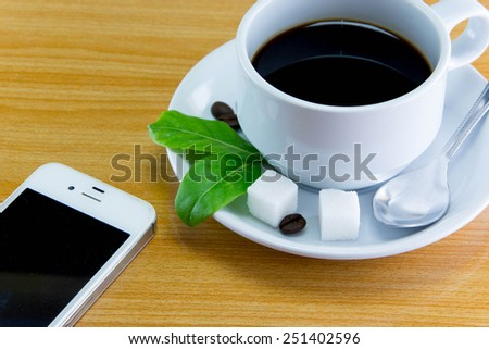 Still life cup of coffee smartphone on wooden table