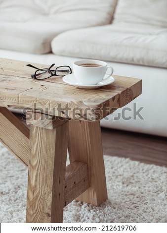 Still life details, cup of coffee on rustic bench over white sofa - stock photo