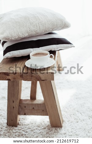 Still life details, stack of black and white cushions on rustic bench on white carpet - stock photo