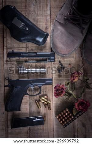 Still Life Disassembled handgun ,Bullet ,Boots, Rose on wood floor. - stock photo