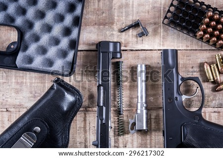 Still Life Disassembled handgun ,Bullet on wood floor.Top view , Vintage Style - stock photo
