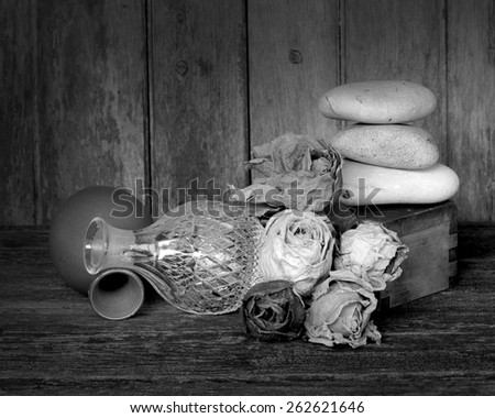 Still life dry roses ceramic crystal stone on old wood black and white version - stock photo