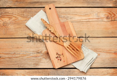 Still life, food and drink concept. Kitchen cooking utensils (knife, fork, cutting board, napkin) on a wooden table. Selective focus, copy space background, top view - stock photo