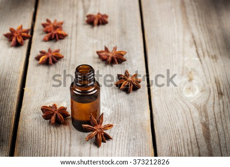 Still life, food and drink, healthcare, beauty concept. Organic anise essential oil on a rustic wooden table. Selective focus - stock photo