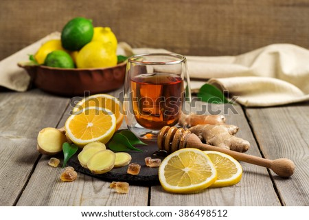 Still life, food and drink, healthcare concept. Ginger tea and ingredients on a black grunge stone table. Selective focus - stock photo