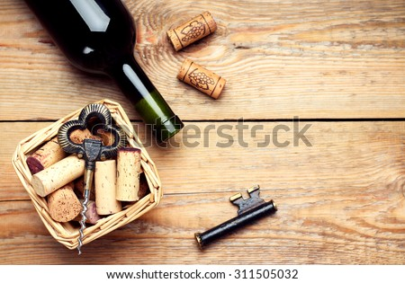 Still life, food and drink, holidays concept. Basket with wine corks, bottle and corkscrew on a wooden table. Selective focus, copy space background, top view - stock photo
