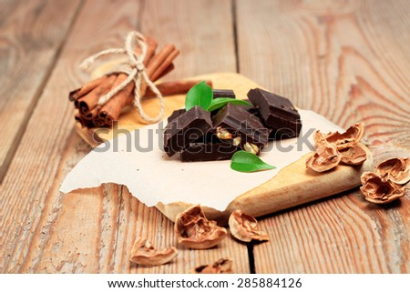 Still life, food and drink, holidays concept. Chocolate bars with cinnamon and walnuts. Selective focus - stock photo
