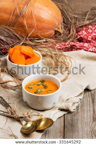 Still life, food and drink, seasonal concept. Fresh orange pumpkin soup in a bowl on a rustic wooden table. Selective focus - stock photo
