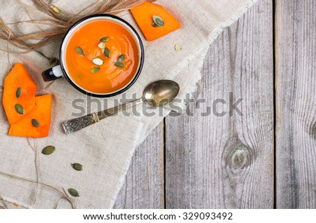 Still life, food and drink, seasonal concept. Fresh orange pumpkin soup in a mug on a rustic wooden table. Selective focus, copy space, top view - stock photo