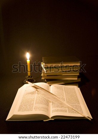 Still life from Bible, piles of books and feather lighted up fire candles.