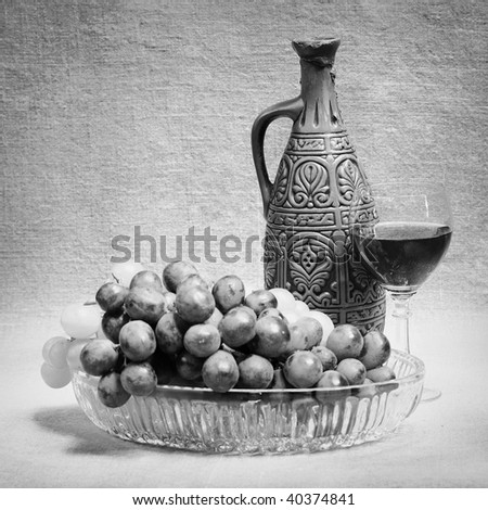 Still-life from grapes, bottle and glass of wine on canvas background - stock photo