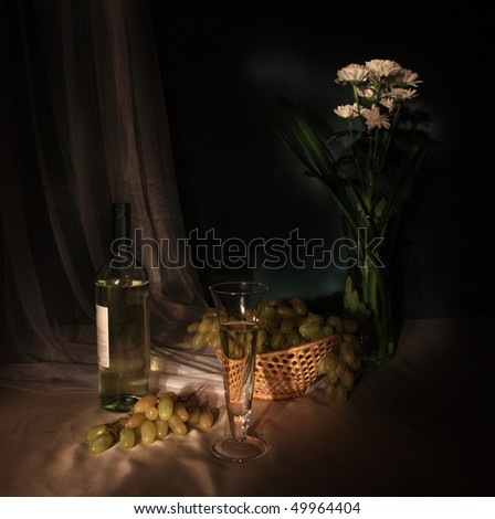Still-life from white wine and grapes - stock photo