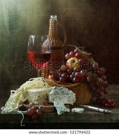 Still-life, glass of fragrant red wine with cheese and juicy ripe fruit - stock photo