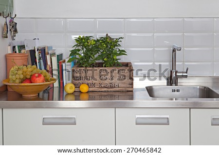 Still life home interior of an elegant family kitchen with fresh fruits and condiments. Elegant house with books, living indoors. Aspirational cooking lifestyle, house interior space property. - stock photo