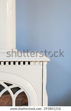 Still life home interior view of a traditional quality wrought iron fireplace in a home living room against a blue wall, indoors. Elegant classic room with a stylish stove, aspirational lifestyle. - stock photo