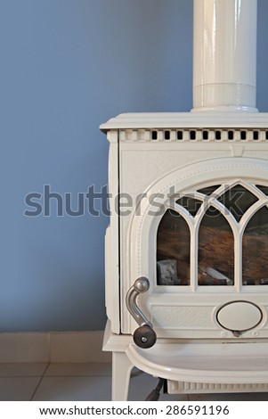 Still life home interior view of a traditional quality wrought iron white fireplace in a stylish home living room against a blue wall, indoors. Elegant classic stove, aspirational lifestyle. - stock photo