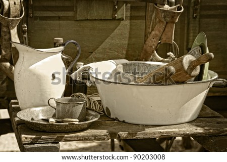 Still life image of vintage cooking utensils and dishes beside an authentic American old west style chuck wagon at an outdoor cooking demonstration (sepia tint added). - stock photo