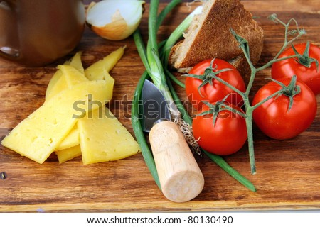 still life in a rustic style, cheese tomatoes and bread on a wooden background - stock photo