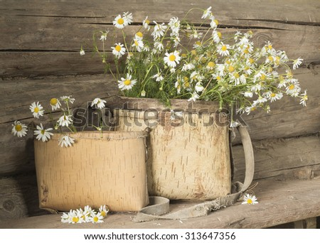 Still life in an old country house. Daisies in a basket made of birch bark.