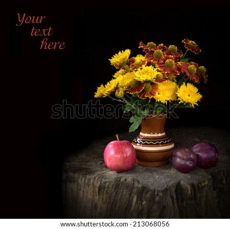 Still life in country style with mysterious night-time lighting. Nosegay of vivid yellow chrysanthemums and red Gaillardias in clay painted vase stands on tree stump near ripe fruits on black backdrop - stock photo