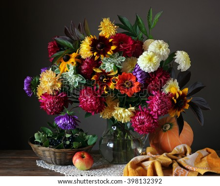 Still life in rustic style with a bouquet of garden flowers in glass jug, pumpkin, Apple and berries on a dark background. - stock photo